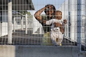 """Une guinŽenne accompagnŽe de ses deux enfants agŽs de onze mois et deux ans et demi est retenue au centre de Retention Administrative (CRA) de Rennes depuis son arrestation ˆ la prŽfecture de Poitiers. Ici dans la cour du CRA, elle Žchange ˆ travers la double rangŽe de grillage avec des membres du MRAP (Mouvement contre le Racisme et pour l'AmitiŽ entre les Peuples) et du RŽseau Education Sans Frontire (RESF). Ceux-ci effectuent regulirement ce qu'ils appellent des """"parloirs sauvages"""". Ils Žchangent mots de rŽconforts et informations avec les dŽtenus . Rennes, FRANCE - 26/09/2008.Ê"""