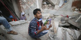 996473-relative-holds-picture-of-a-garment-worker-in-front-of-the-rubble-of-the-collapsed-rana-plaza-buildi